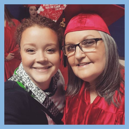 Woman graduating taking a selfie with younger woman